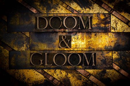 Doom and Gloom text formed with real authentic typeset letters on vintage textured silver grunge copper and gold background