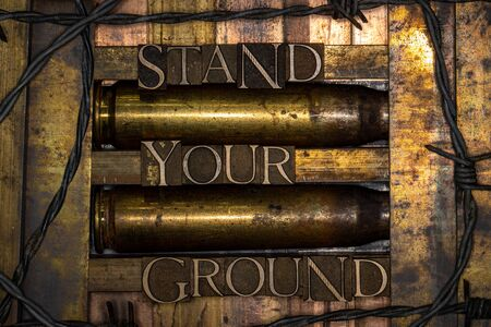 Stand Your Ground text with bullet casings and barbed wire formed with real authentic typeset letters on vintage textured silver grunge copper and gold background