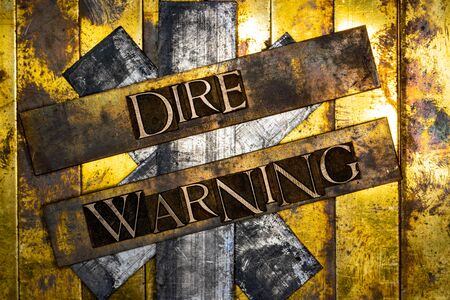 Dire Warning text formed with real authentic typeset letters on vintage textured silver grunge copper and gold background