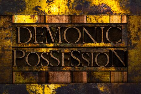 Demonic Possession text formed with real authentic typeset letters on vintage textured silver grunge copper and gold background Archivio Fotografico