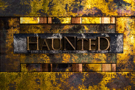 Haunted text formed with real authentic typeset letters on vintage textured silver grunge copper and gold background