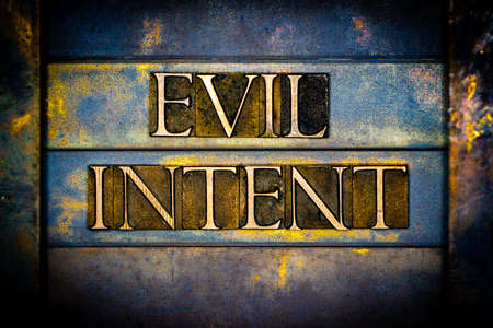 Evil Intent text formed with real authentic typeset letters on vintage textured silver grunge copper and gold background