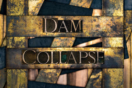 Dam Collapse text formed with real authentic typeset letters on vintage textured silver grunge copper and gold background