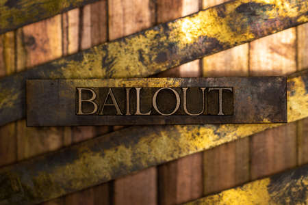 Bailout text formed with real authentic typeset letters on vintage textured silver grunge copper and gold background
