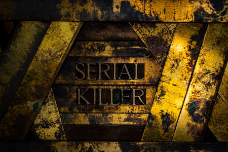 Serial Killer text formed with real authentic typeset letters on vintage textured silver grunge copper and gold background