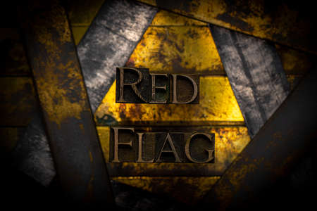 Red Flag text formed with real authentic typeset letters on vintage textured silver grunge copper and gold background