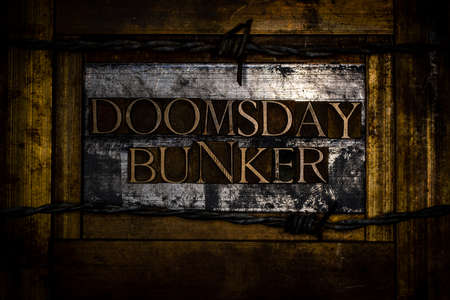 Doomsday Bunker text formed with real authentic typeset letters on vintage textured silver grunge copper and gold background