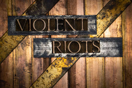Violent Riots text formed with real authentic typeset letters on vintage textured silver grunge copper and gold background