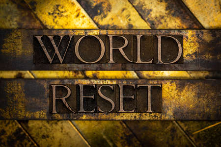 World Reset text formed with real authentic typeset letters on vintage textured silver grunge copper and gold background