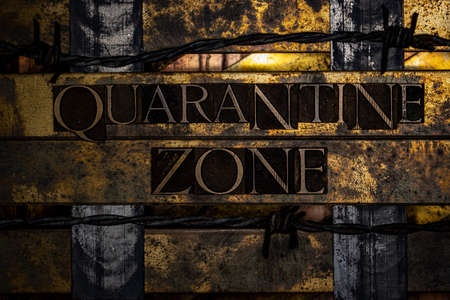 Quarantine Zone text formed with real authentic typeset letters on vintage textured silver grunge copper and gold background Stock Photo