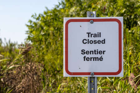 Trail closed sign in English and French with overgrown trail in background Фото со стока