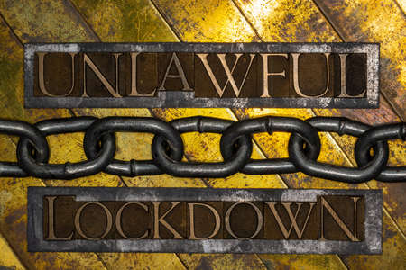 Unlawful Lockdown text formed by real authentic typeset letters with steel chain on vintage textured grunge copper and gold background