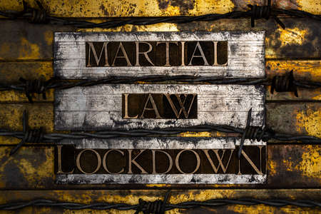 Martial Law Lockdown text formed with real authentic typeset letters with barbed wire on vintage textured silver grunge copper and gold background Standard-Bild