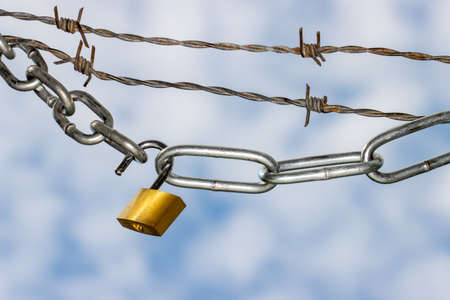 Padlock and steel chains with barbed wire against blue clouded sky symbolizing lockdown