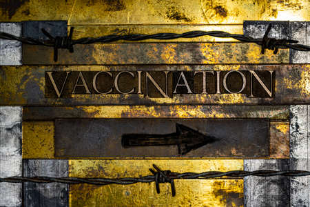 Vaccination text message on textured grunge copper and vintage gold sign with charcoal black arrow Stock Photo