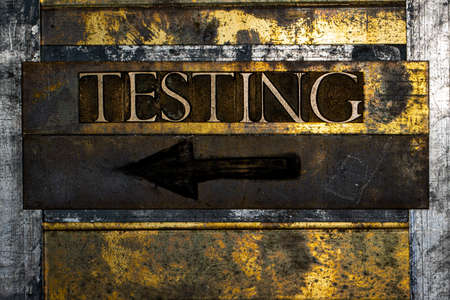 Testing sign with black charcoal arrow on textured grunge copper and vintage gold background with barbed wire 免版税图像 - 156046988