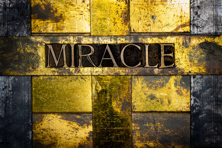 Miracle text message on textured grunge copper and vintage gold background 写真素材