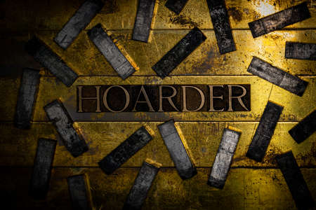 Hoarder text formed with real authentic typeset letters on vintage textured silver grunge copper and gold background Stock fotó