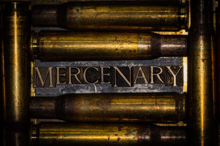 Mercenary text message on lead bar between copper 50 caliber gun casings on vintage textured grunge copper and gold background Banque d'images