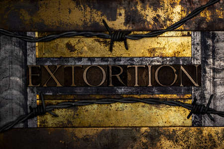 Extortion text message on textured grunge copper and vintage gold background lined with barbed wire