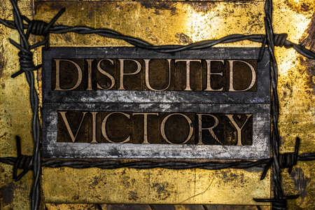 Disputed Victory text message on textured grunge copper and vintage gold background surrounded by barbed wire Stock fotó