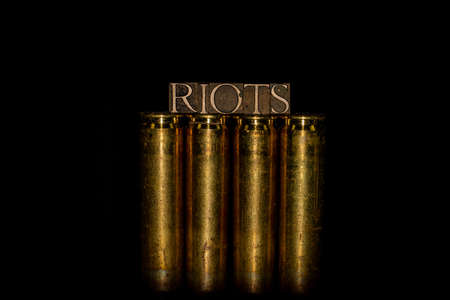 Riots text formed with real authentic typeset letters on 50 caliber BMG bullet casings with black background Stock fotó
