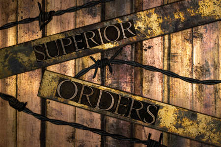 Superior Orders or Befehl ist Befehl text message on textured bronze grunge copper and vintage gold background with barbed wire
