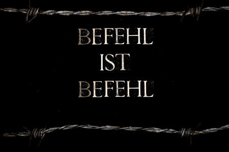 Befehl ist Befehl or Superior Orders text on black background lined with barbed wire