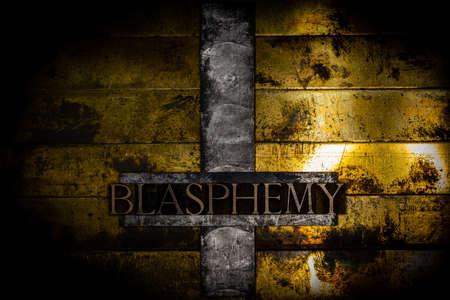 Blasphemy text message on upturned lead cross with textured grunge vintage gold background