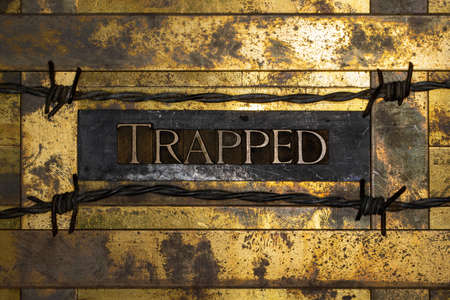 Trapped text message on textured grunge copper and vintage gold background lined with barbed wire Stockfoto