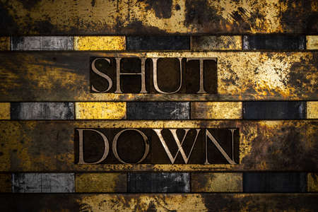 Shut Down text message on vintage textured grunge copper and gold background