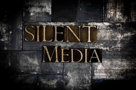 Silent Media text on vintage textured grunge copper and gold background Stok Fotoğraf