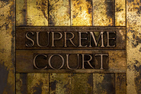 Supreme Court text message on lead bar on textured grunge copper and vintage gold background