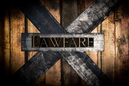 Lawfare text formed by real authentic typeset letters on vintage textured grunge bronze background