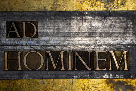 Ad Hominem text message on lead bar on textured grunge copper and vintage gold background