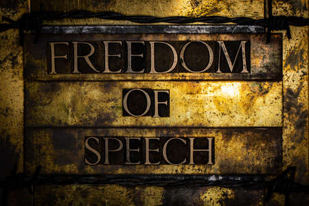 Freedom Of Speech text with barbed wire on textured grunge copper and vintage gold background