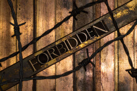 Forbidden text over barbed wire on grunge bronze with textured copper and gold background