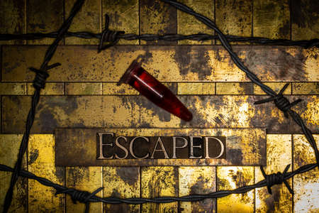 Escaped text with red fluid filled laboratory vial on vintage textured grunge copper and gold background surrounded by barbed wire