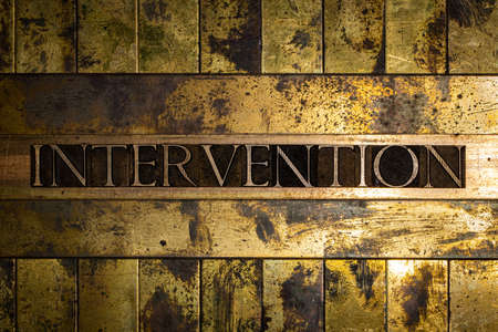 Intervention text formed with real authentic typeset letters on vintage textured silver grunge copper and gold background