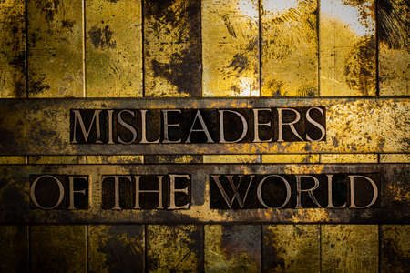 Misleaders Of The World text on grunge textured copper and gold background Stockfoto
