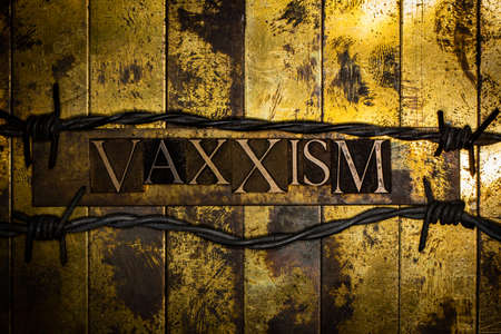 Vaxxism text formed with real authentic typeset letters on vintage textured silver grunge copper and gold background