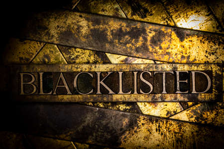 Blacklisted text formed with real authentic typeset letters on vintage textured silver grunge copper and gold background