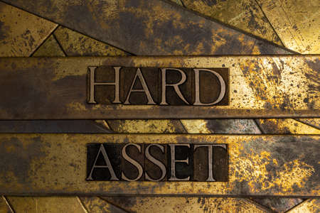 Hard Asset text on textured grunge copper and vintage gold background Stockfoto