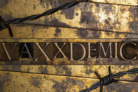 Vaxxdemic text formed with real authentic typeset letters on vintage textured silver grunge copper and gold background Stockfoto