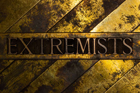 Extremists text message on vintage textured grunge copper and gold background