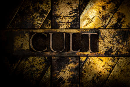 Cult text on vintage textured grunge copper and gold background Stockfoto