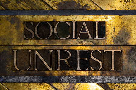 Social Unrest text on vintage textured grunge copper and gold background