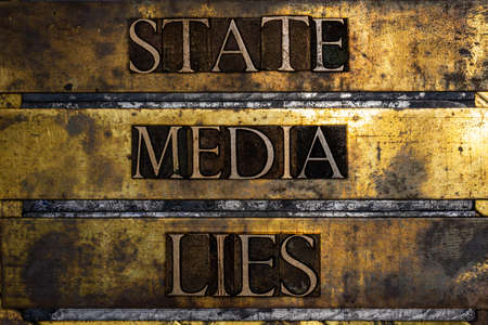 State Media Lies text message on vintage textured grunge copper and gold background