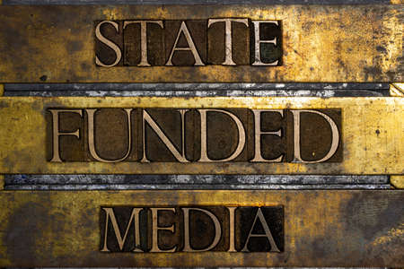 State Funded Media text message on vintage textured grunge copper and gold background