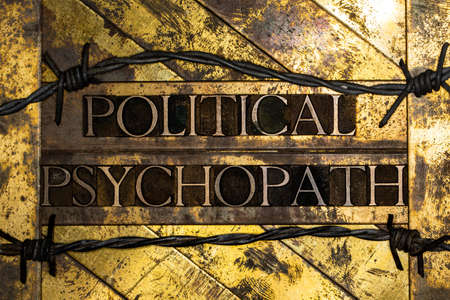Political Psychopath text on vintage textured silver grunge copper and gold background with barbed wire